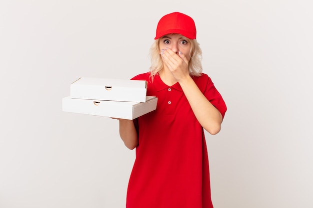 Jonge mooie vrouw die mond bedekt met handen met een geschokt. pizza bezorgconcept