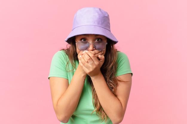 Jonge mooie vrouw die mond bedekt met handen met een geschokt. zomer concept