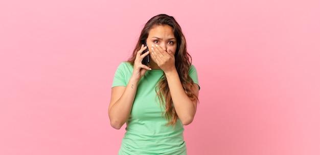 Jonge mooie vrouw die mond bedekt met handen met een geschokte en een slimme telefoon vasthoudt