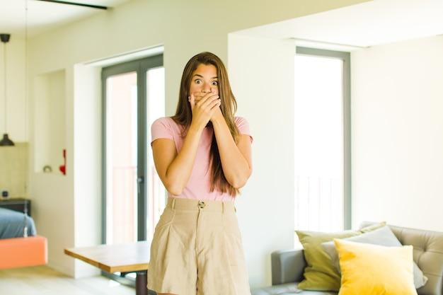 Jonge mooie vrouw die mond bedekt met handen met een geschokte, verbaasde uitdrukking, een geheim bewaren of oeps zeggen