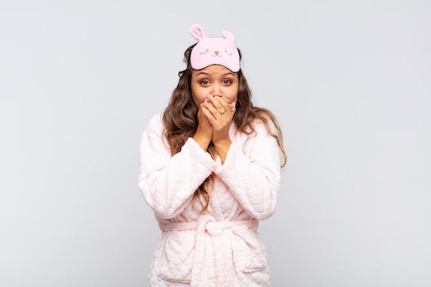 Jonge mooie vrouw die mond bedekt met handen met een geschokte, verbaasde uitdrukking, een geheim houdt of oeps zegt in een pyjama