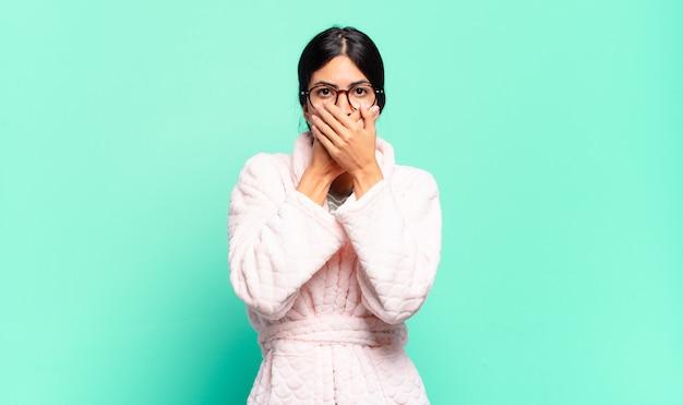 Jonge mooie vrouw die mond bedekt met handen met een geschokte, verbaasde uitdrukking, een geheim houdt of oeps zegt. pyjama concept