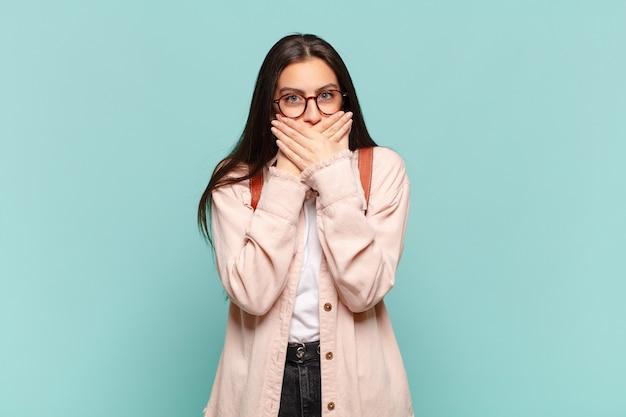 Jonge mooie vrouw die mond bedekt met handen met een geschokte, verbaasde uitdrukking, een geheim houdt of oeps zegt. studentenconcept