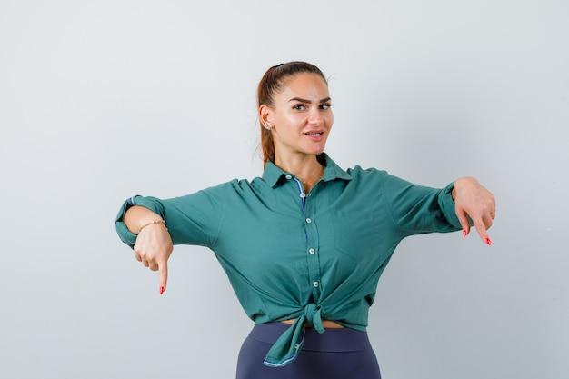 Jonge mooie vrouw die naar beneden wijst in een groen shirt en er vrolijk uitziet, vooraanzicht.