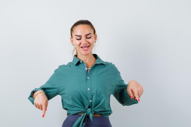 Jonge mooie vrouw die naar beneden wijst in een groen shirt en er vrolijk uitziet. vooraanzicht.