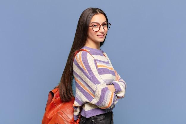 Jonge mooie vrouw die naar camera glimlacht met gekruiste armen en een gelukkige, zelfverzekerde, tevreden uitdrukking, zijaanzicht. student concept