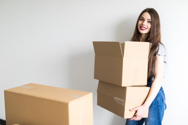 Jonge mooie vrouw die naar een nieuw appartement verhuist met kartonnen dozen met spullen
