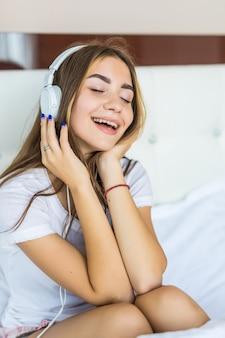 Jonge mooie vrouw die naar muziek luistert in een koptelefoon op bed