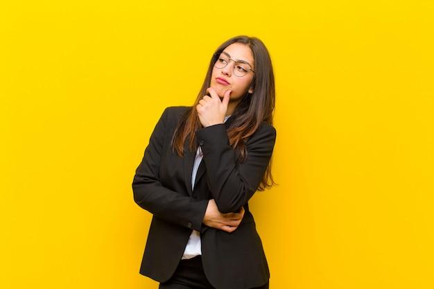 Jonge mooie vrouw die nadenkende, ideeën benieuwd zijn of veronderstellen, dagdromen en omhoog aan copyspace tegen oranje muur kijken