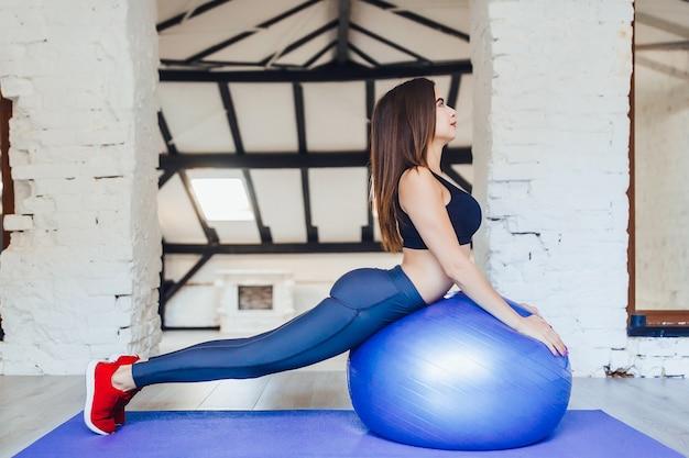 Jonge mooie vrouw die oefening met pilatesbal doet bij witte gymnastiek.