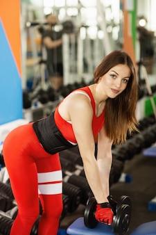 Jonge mooie vrouw die oefeningen met domoor in gymnastiek doet. het blije glimlachende meisje geniet van met haar opleidingsproces