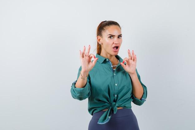 Jonge mooie vrouw die ok gebaar in groen shirt toont en perplex kijkt. vooraanzicht.