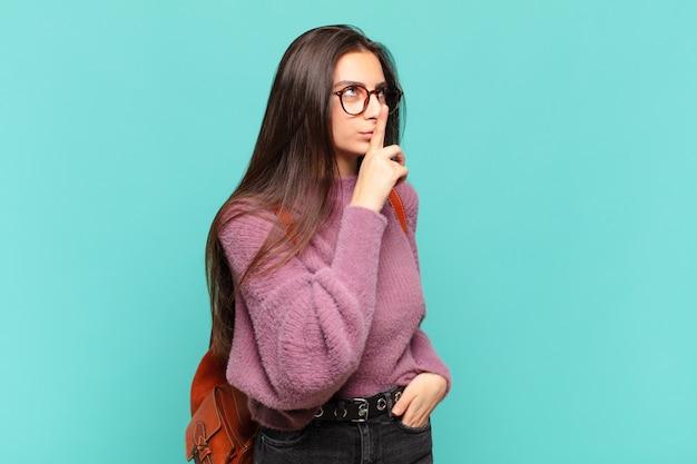 Jonge mooie vrouw die om stilte en stilte vraagt, met de vinger voor de mond gebarend, shh zegt of een geheim houdt. studentenconcept