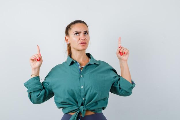 Jonge mooie vrouw die omhoog wijst in een groen shirt en peinzend kijkt, vooraanzicht.