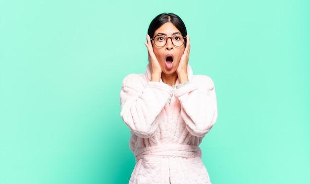 Jonge mooie vrouw die onaangenaam geschokt, bang of bezorgd kijkt, met wijd open mond en beide oren bedekt met handen. pyjama's concept