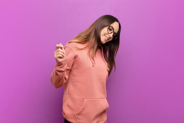 Jonge mooie vrouw die, onbezorgd, ontspannen en gelukkig, het dansen en het luisteren aan muziek glimlachen, die pret hebben op een partij tegen purpere muur