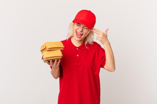 Jonge mooie vrouw die ongelukkig en gestrest kijkt, zelfmoordgebaar dat pistoolteken maakt. hamburger bezorgconcept