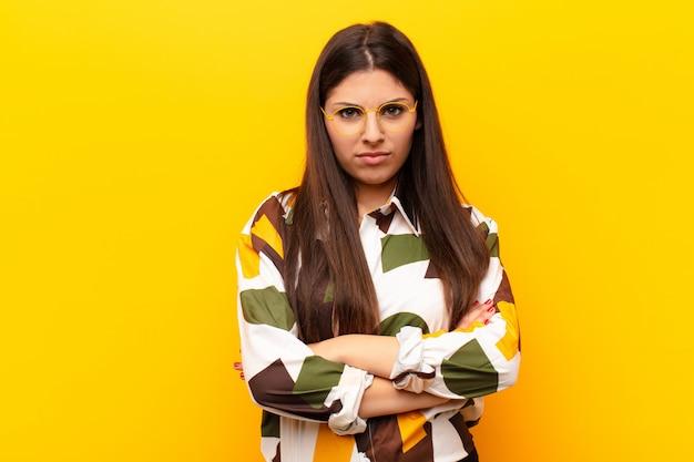 Jonge mooie vrouw die ontevreden en teleurgesteld voelen, die ernstig, geërgerd en boos met gekruiste wapens tegen gele muur kijken