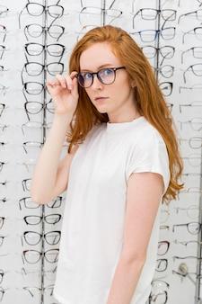 Jonge mooie vrouw die oogglazen in opticienwinkel kiezen