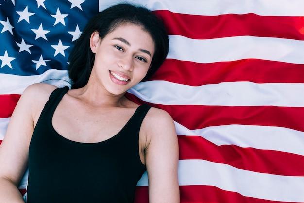 Jonge mooie vrouw die op amerikaanse vlag ligt