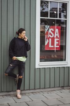 Jonge mooie vrouw die op de smartphone spreekt.