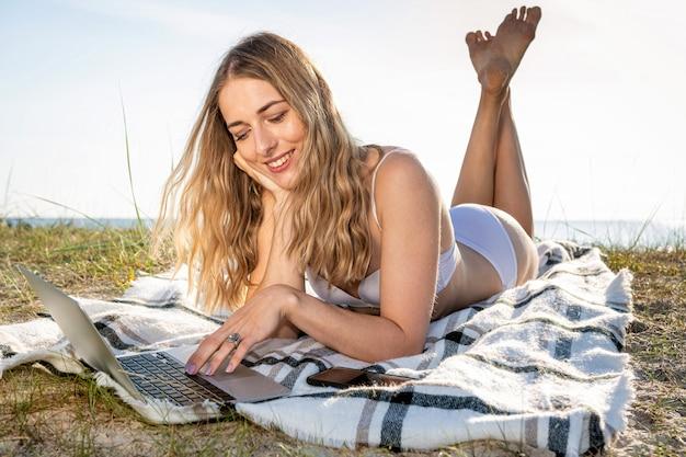 Jonge mooie vrouw die op het strand zonnebaadt en aan computer werkt