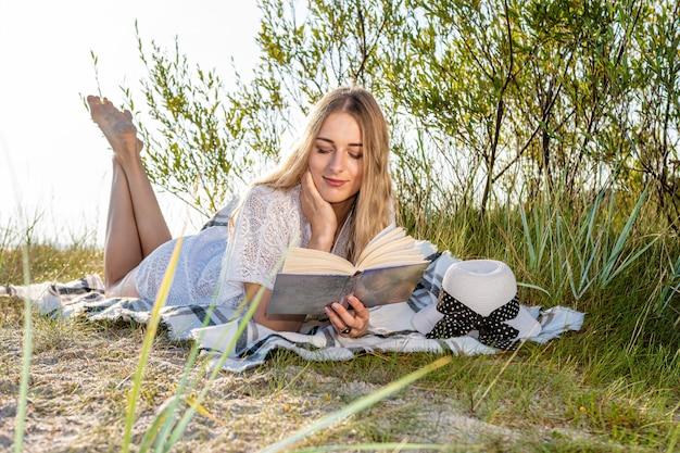 Jonge mooie vrouw die op het strand zonnebaadt en een boek leest