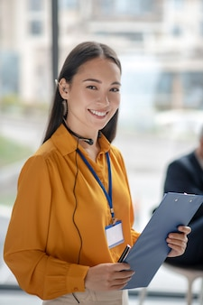 Jonge mooie vrouw die op het werk glimlacht
