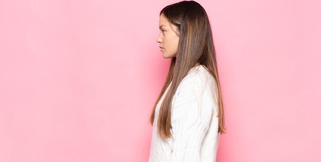 Jonge mooie vrouw die op profielweergave ruimte vooruit wil kopiëren, denken, zich voorstellen of dagdromen