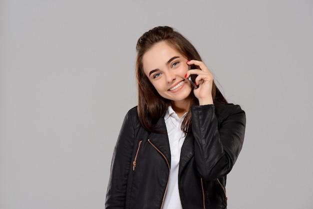 Jonge mooie vrouw die op telefoon spreekt, die over purpere muur glimlacht