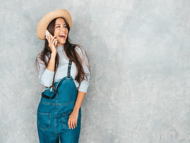 Jonge mooie vrouw die op telefoon spreekt. trendy meisje in casual zomer overall kleding en hoed.