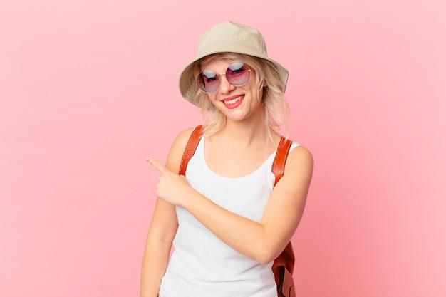 Jonge mooie vrouw die opgewonden en verrast kijkt die naar de kant wijst. zomer toeristische concept