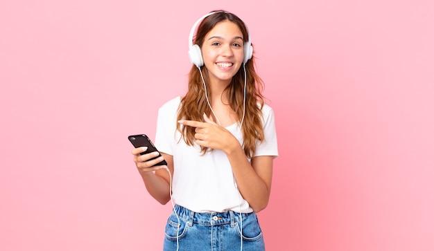 Jonge mooie vrouw die opgewonden en verrast kijkt en naar de zijkant wijst met een koptelefoon en een smartphone