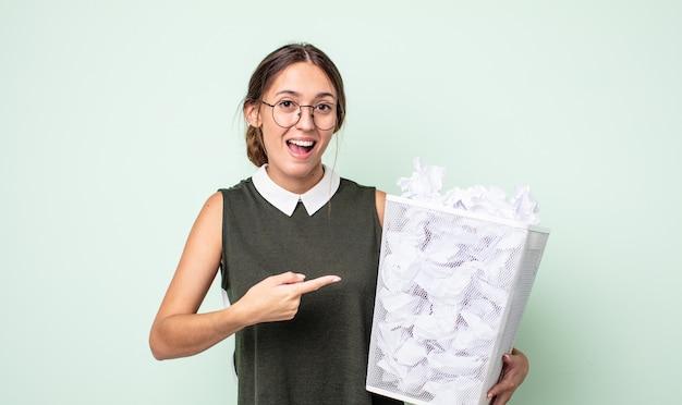 Jonge mooie vrouw die opgewonden en verrast kijkt en naar de zijkant wijst. papier ballen prullenbak concept