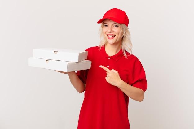 Jonge mooie vrouw die opgewonden en verrast kijkt en naar de zijkant wijst. pizza bezorgconcept