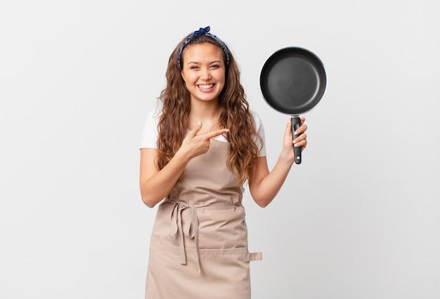 Jonge mooie vrouw die opgewonden en verrast kijkt, wijst naar het concept van de zijkok en houdt een pan vast