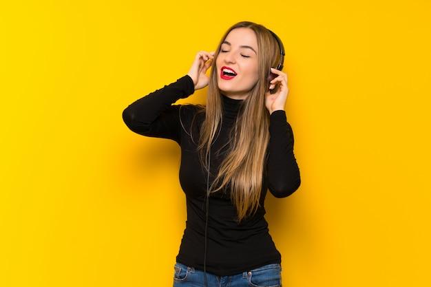 Jonge mooie vrouw die over gele muur aan muziek met hoofdtelefoons luistert