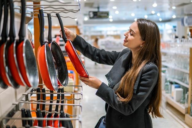 Jonge mooie vrouw die pan gebruiksvoorwerpen kiest in een winkel supermarkt winkel.