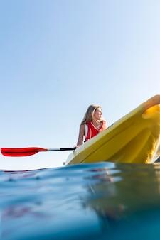 Jonge mooie vrouw die per kano reist