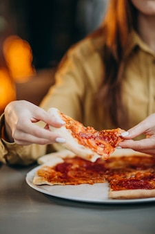 Jonge mooie vrouw die pizza eet bij een bar