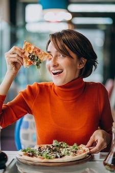 Jonge mooie vrouw die pizza eet bij pizzabar