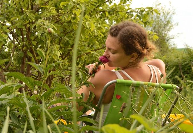 Jonge mooie vrouw die pret het snuiven bloemen hebben die op een stoel in de tuin op een de zomerdag zitten