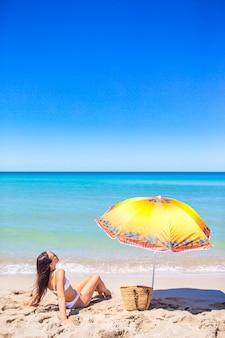 Jonge mooie vrouw die pret op tropische kust met de blauwe hemel en het turkooise water in de zee heeft