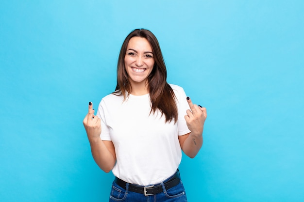 Jonge mooie vrouw die provocerend, agressief en obsceen voelt, de middelvinger omdraait, met een rebelse houding tegen de blauwe muur