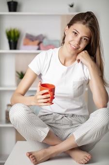 Jonge mooie vrouw die pyjama draagt die kop koffie drinkt.
