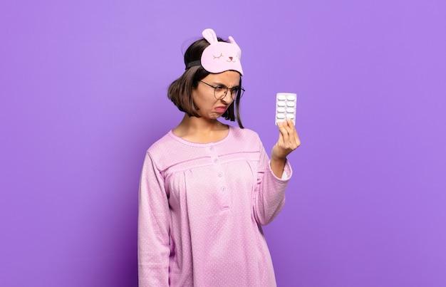 Jonge mooie vrouw die pyjama's draagt en pillen houdt