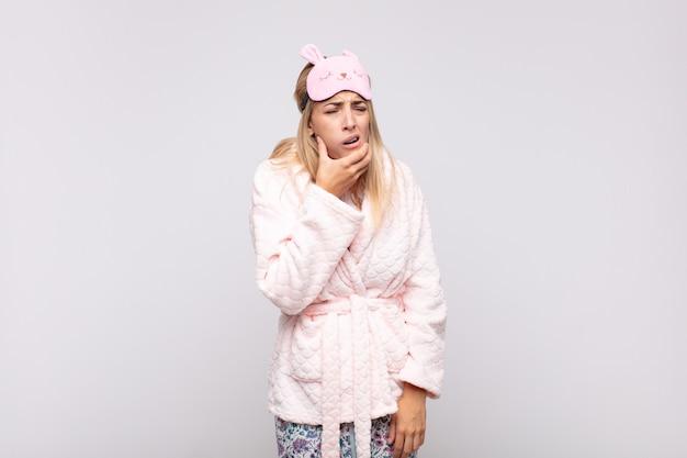 Jonge mooie vrouw die pyjama's draagt, met wijd open mond en ogen en hand op kin