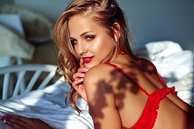 Jonge mooie vrouw die rode lingerie op bed in de ochtend draagt