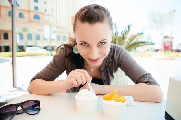 Jonge mooie vrouw die roomijs eet