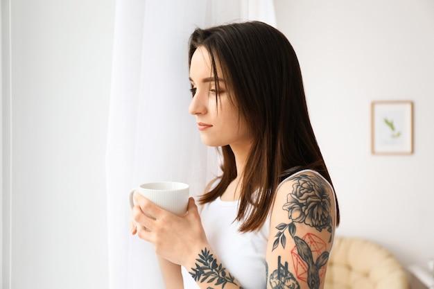 Jonge mooie vrouw die 's ochtends thuis koffie drinkt